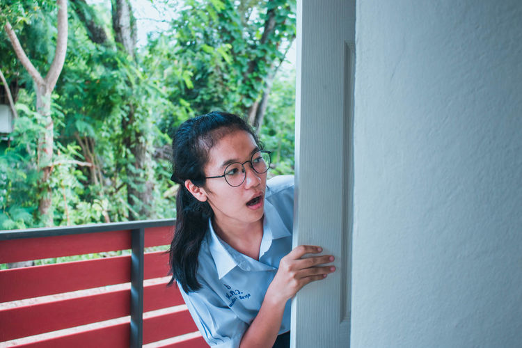 Shocked young woman peeking at balcony