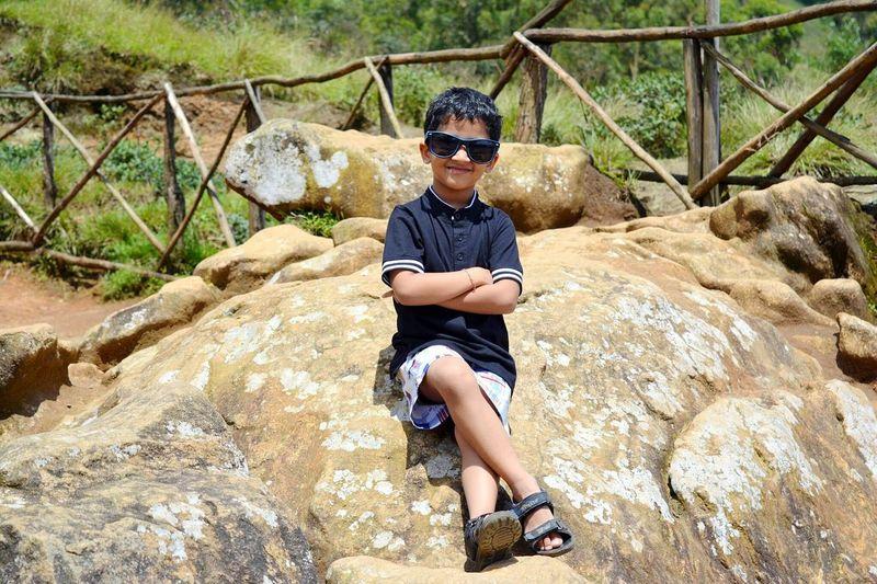 Full length of boy sitting on rock