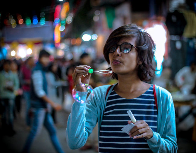 Close-up of woman blowing bubbles