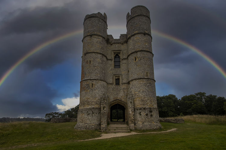 Castle on field against rainbow in sky