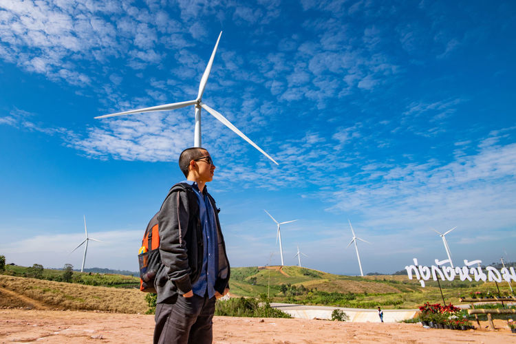 Low angle view of man looking away while standing against wind turbine