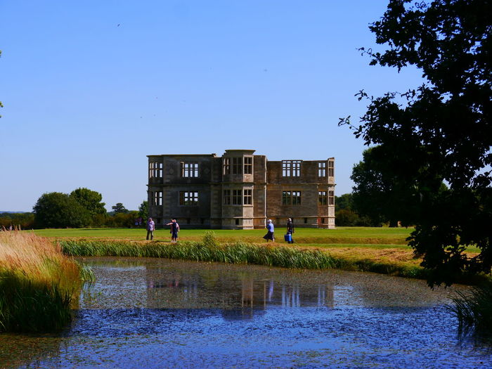 Architecture Beauty In Nature Building Exterior Built Structure Clear Sky Day Grass Growth Lyveden New Bield National Trust National Trust 🇬🇧 Nature Outdoors Real People Sky Tree Water