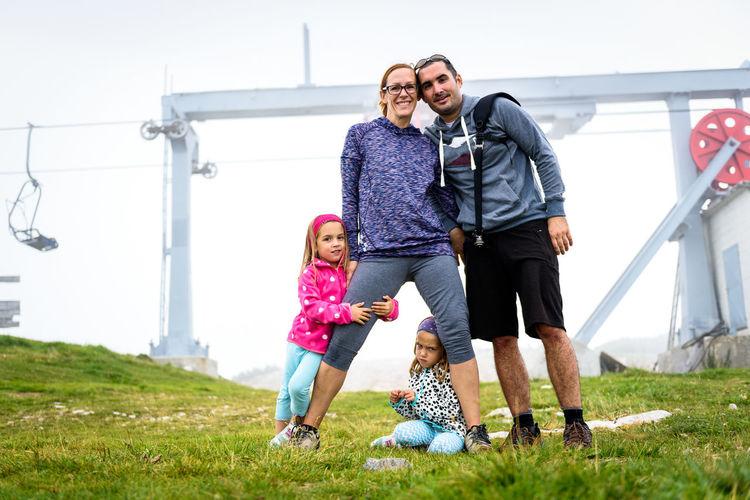 Full length of family standing on field against clear sky