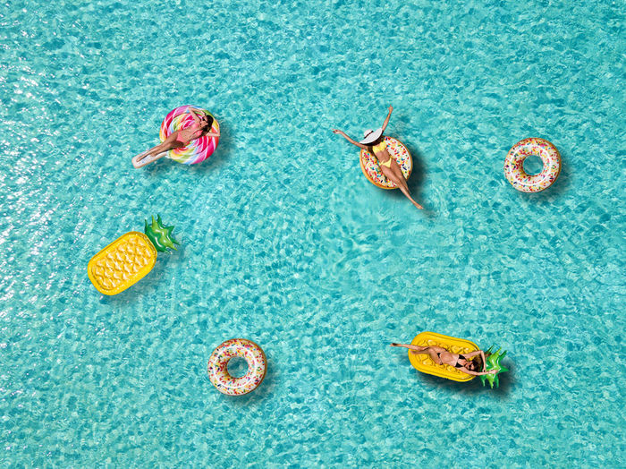 High angle view of female friends relaxing on pool rafts in sea