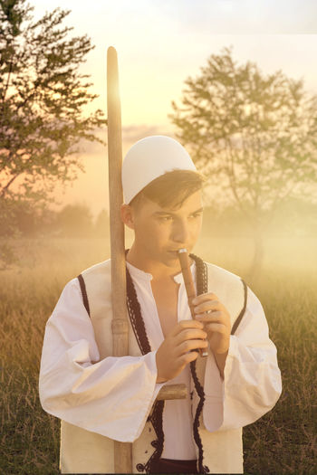 young man in traditional albanian costume playing flute in front of nature meadow and evening dusk Albania Albanian Field Kosovo Traditional Clothing Cap Evening Mist Flute Fog Kosova Leisure Activity Meadow Nature One Person Playing Music Shepherd Standing Sunset Sunshine Traditional Costume Tree Warm