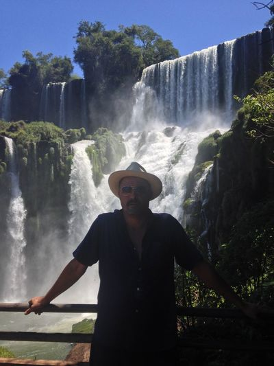Portrait of man standing against waterfall in forest