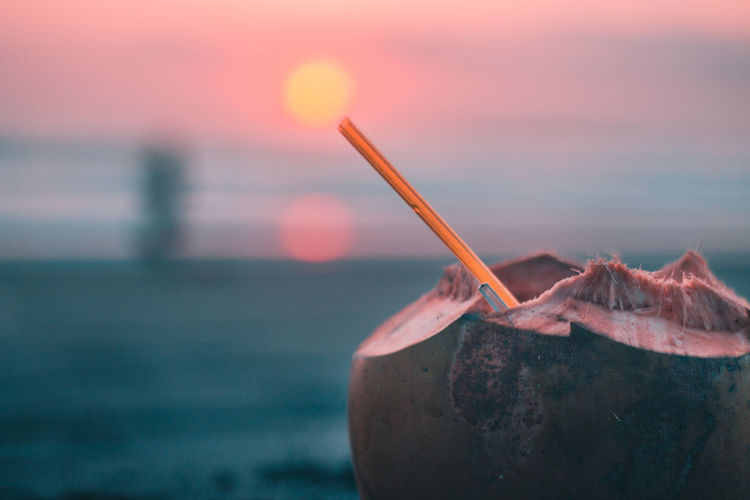 Close-up of coconut with straw against sky during sunset