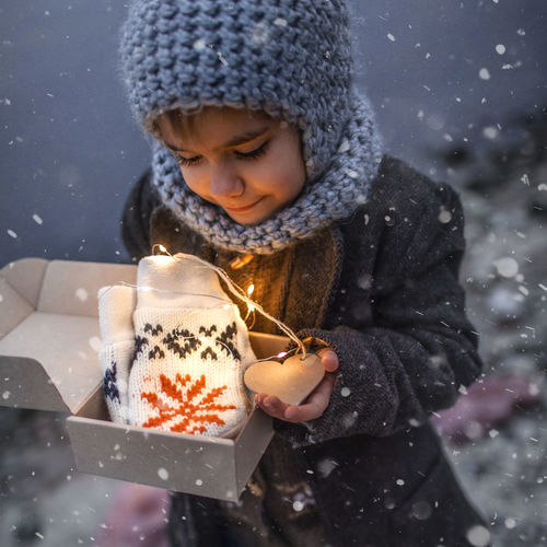 Pretty girl in knitted grey hat opening a crafted gift box with a new pair of gloves, snowfall