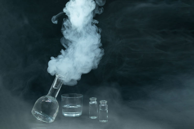Close-up of smoke emitting from container on table
