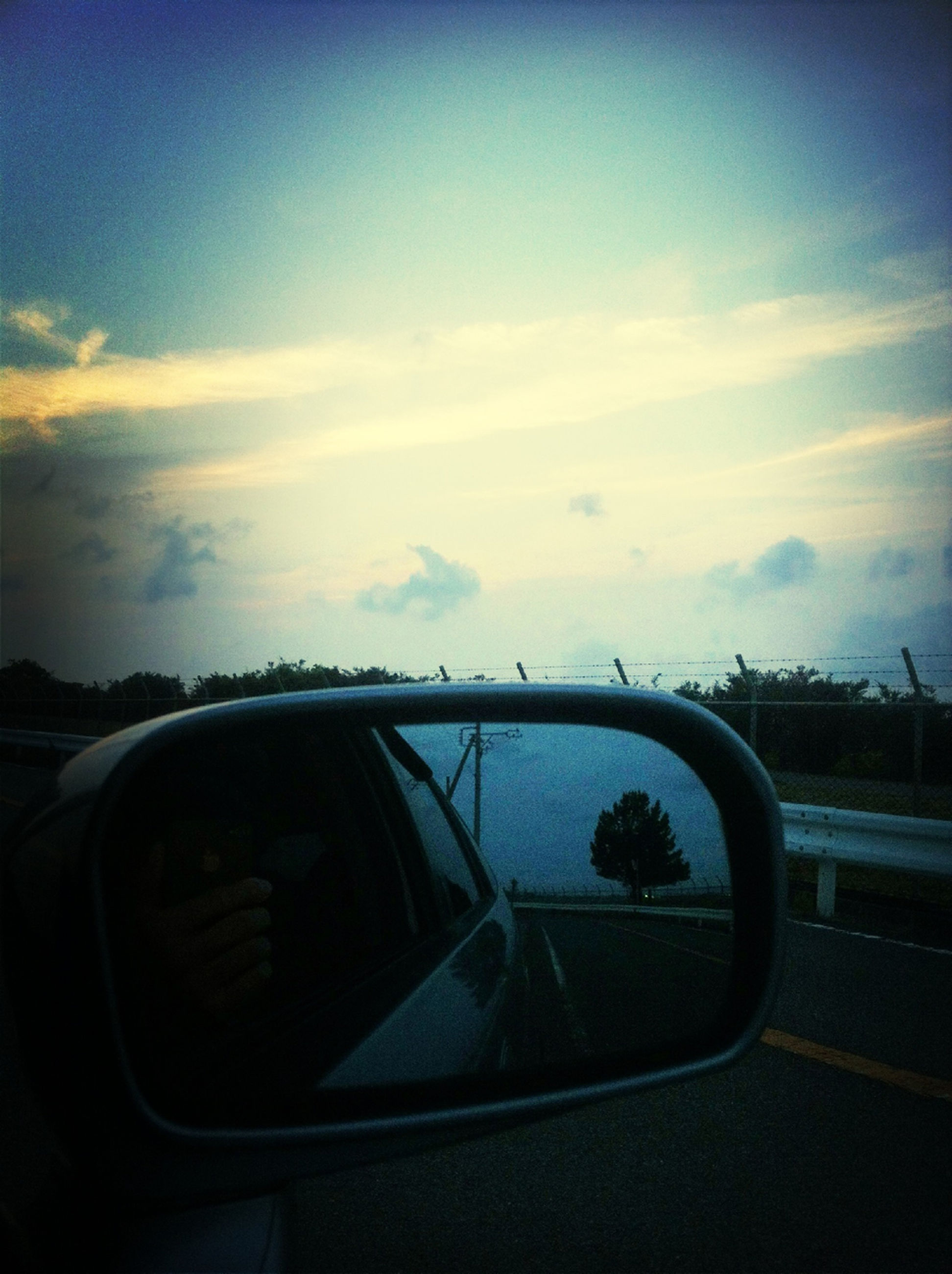 transportation, land vehicle, mode of transport, car, sky, road, sunset, cloud - sky, on the move, travel, cloud, street, side-view mirror, vehicle interior, windshield, car interior, dusk, highway, silhouette, glass - material