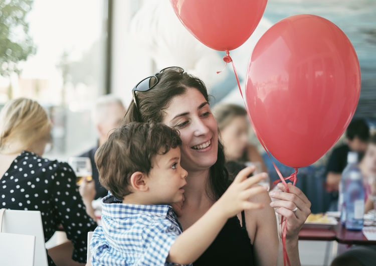 Smiling Mother And Son Holding Balloons