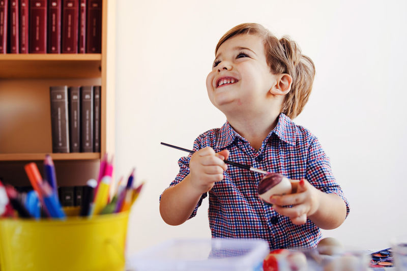 Smiling boy painting easter egg at home