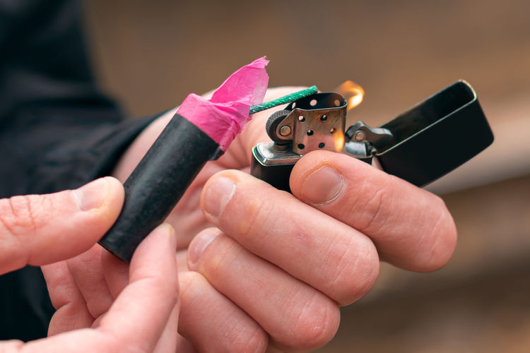 Close-up of man igniting firecracker outdoors