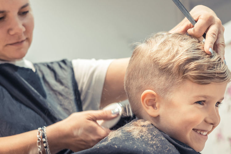 Close-up of female hairdresser styling boy hair in salon