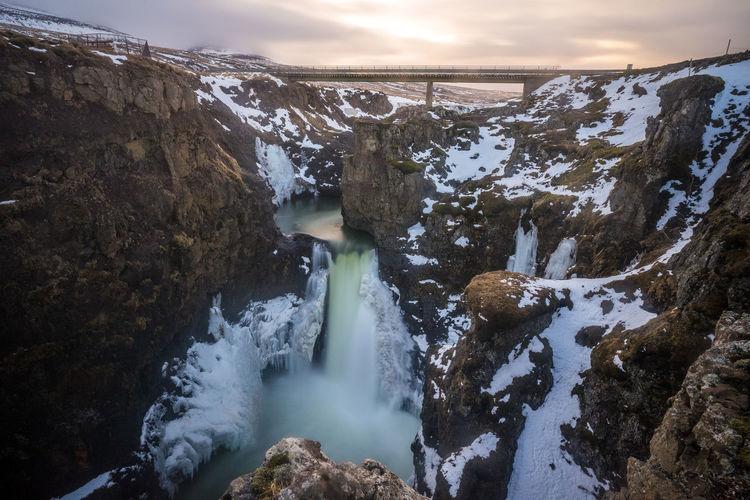 Water flowing through rocks against sky