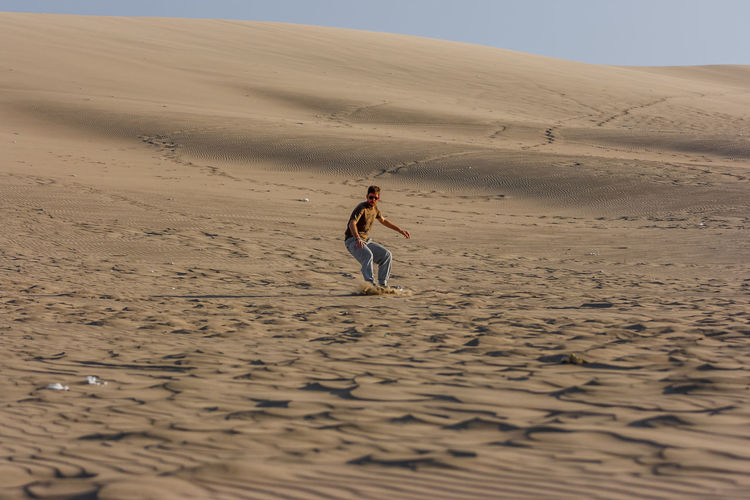 Picture of a young man sandboarding at sunset, Huacachina, Ica, Peru Desert Dunes Fun Man Peru Surf Huacachina Ica Land Leisure Activity Lifestyles Nature Outdoors Sand Sand Dune Sand Surfing Sport Vacations