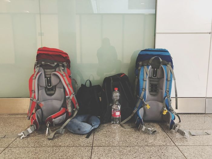 Backpacks at the Airport Backpacking Backpack EyeEm Selects No People Still Life Shoe Day Absence Wall - Building Feature Luggage Architecture Travel Personal Accessory Pair