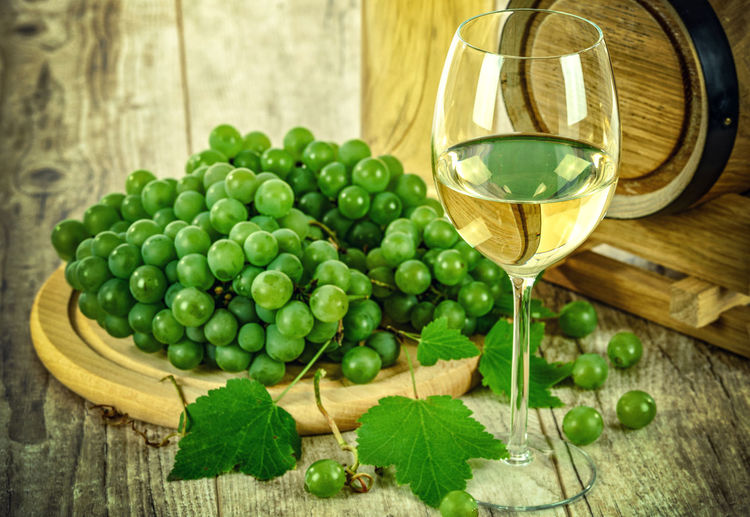 Close-up of grapes by wineglass on table