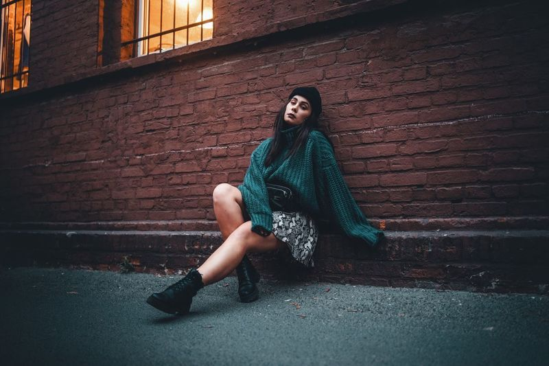 One Person Full Length Wall Portrait Looking At Camera Young Adult Brick Casual Clothing Brick Wall Wall - Building Feature Lifestyles Real People Architecture Sitting Fashion Front View Leisure Activity Built Structure Young Women Beautiful Woman Hair Outdoors Hairstyle Teenager