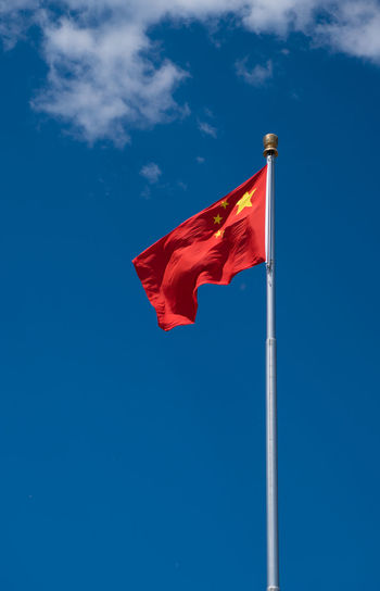 Low angle view of chinese flag waving against blue sky