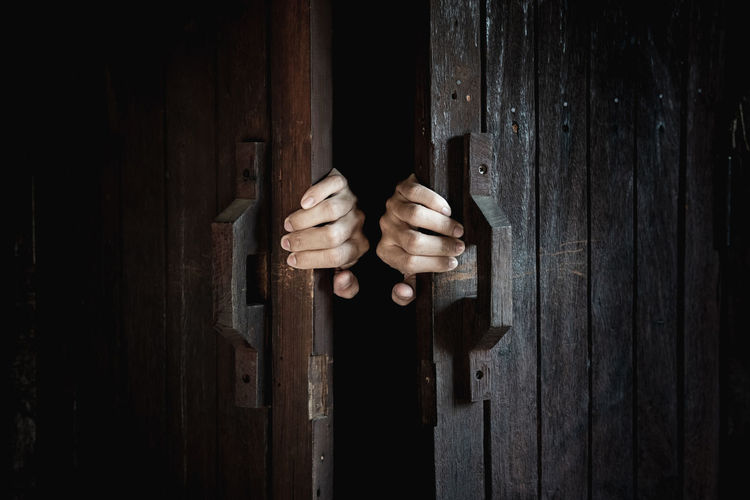 Cropped hands of person closing door