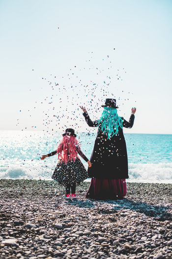 Rear view of mother and daughter standing at beach against clear sky and throwing confettis
