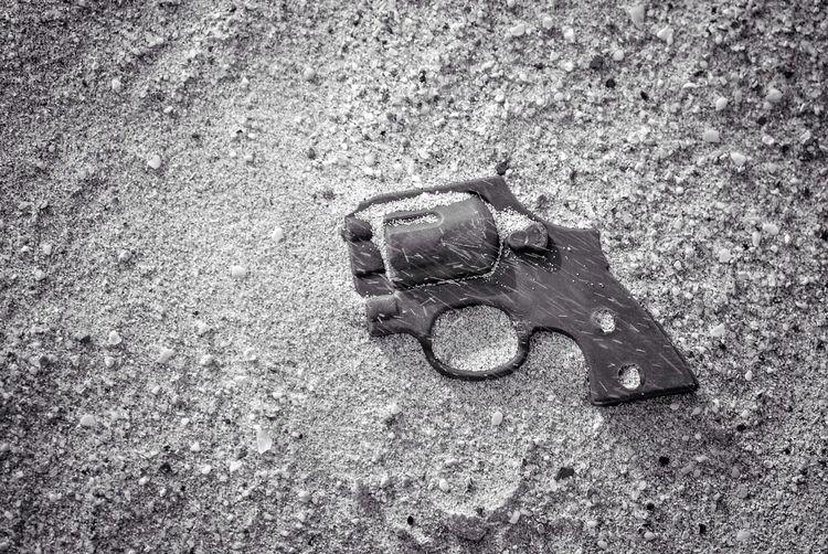 High angle view of broken gun on sand