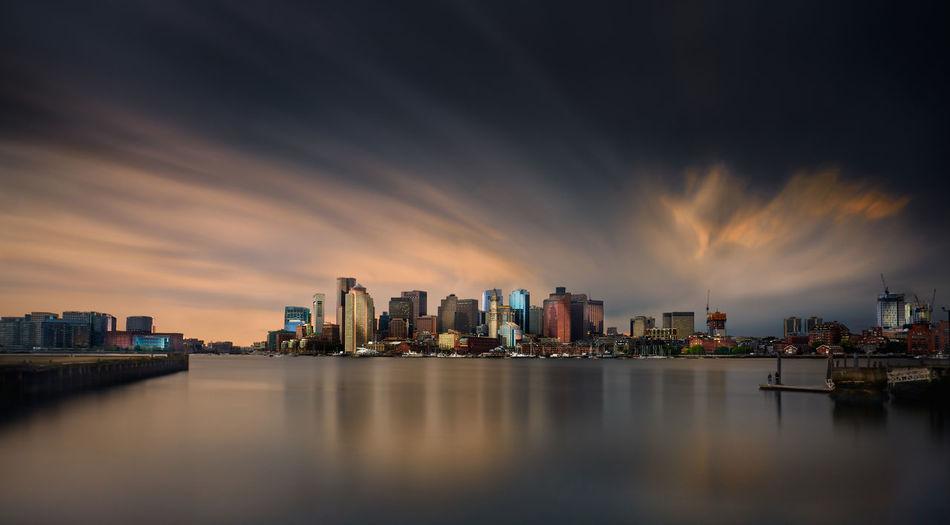 Sea by buildings against sky during dusk