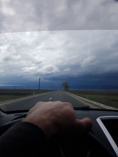 Car Car Interior Cloud - Sky Diminishing Perspective Driving Finger Glass - Material Hand Human Body Part Human Hand Land Vehicle Mode Of Transportation Motor Vehicle Nature One Person Outdoors Real People Road Sky Transparent Transportation Vehicle Interior Windshield
