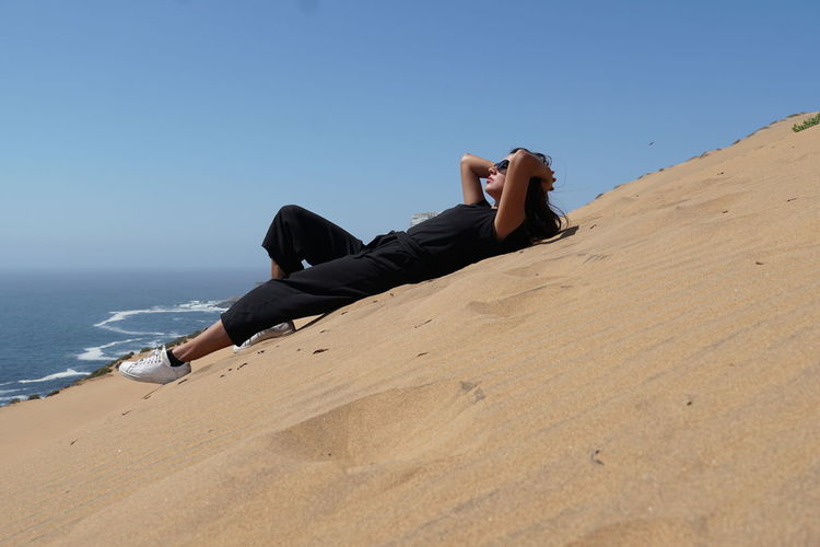 Woman relaxing on beach against clear sky