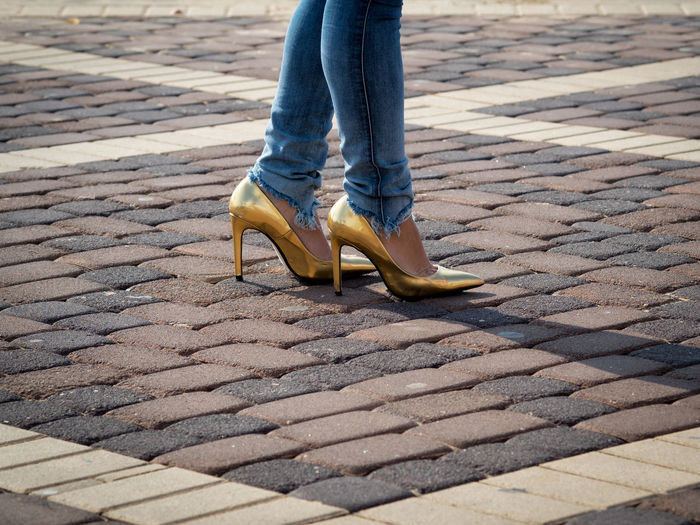 Low section of woman wearing high heels shoe on paved street