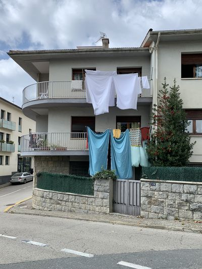 Clothes drying on footpath by building against sky