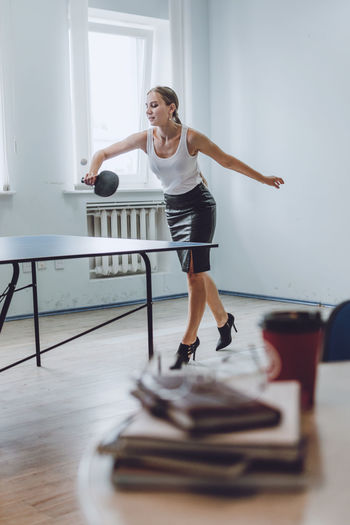 Full length of businesswoman playing tablet tennis in office