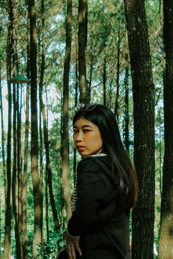 Side view of young woman standing by tree trunk in forest