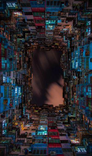 Directly below shot of buildings against sky at night