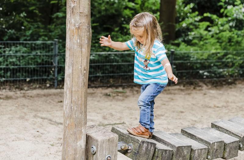 Full length of girl walking on wood in park