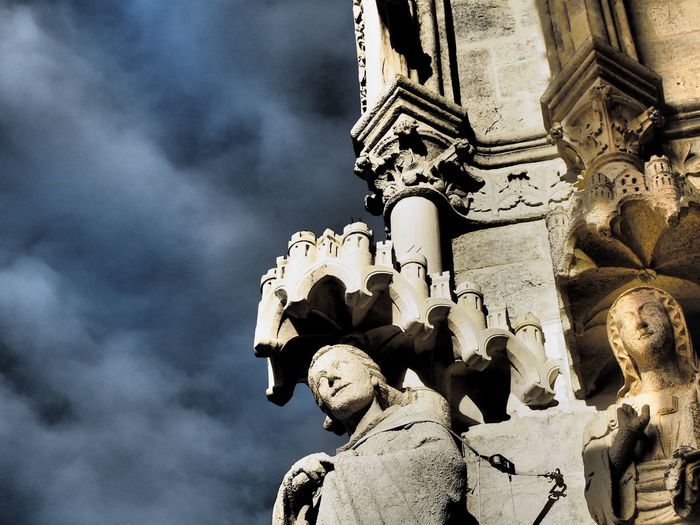 Statues on cropped wall against clouds