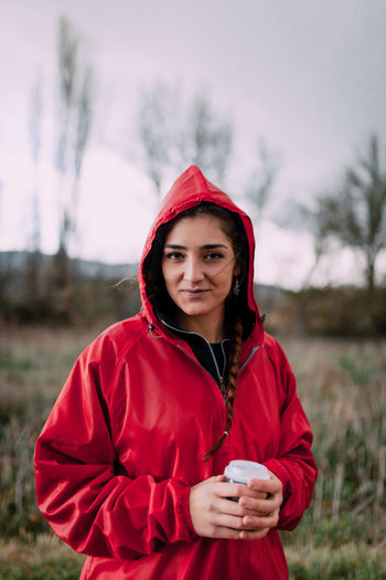 Smiling girl wearing a red raincoat on the field Raincoat Red Raining Girl Young Woman Attractive Field One Person Only Millennial Pink Brunette Braid Cold Temperature Gooseflesh Goose Pimples Beautiful Woman Hood - Clothing Warm Clothing Drink Leisure Activity Cup Young Women Focus On Foreground Holding Waist Up Lifestyles Standing Young Adult Looking At Camera Real People Clothing Portrait Front View One Person Cloudy Day