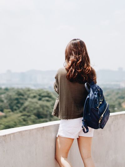 See the world while you still can Leisure Activity Real People Rear View Lifestyles One Person Casual Clothing Three Quarter Length Women Nature Day Hairstyle Hair Outdoors Focus On Foreground Retaining Wall Sky Looking At View Adult Young Women Bag