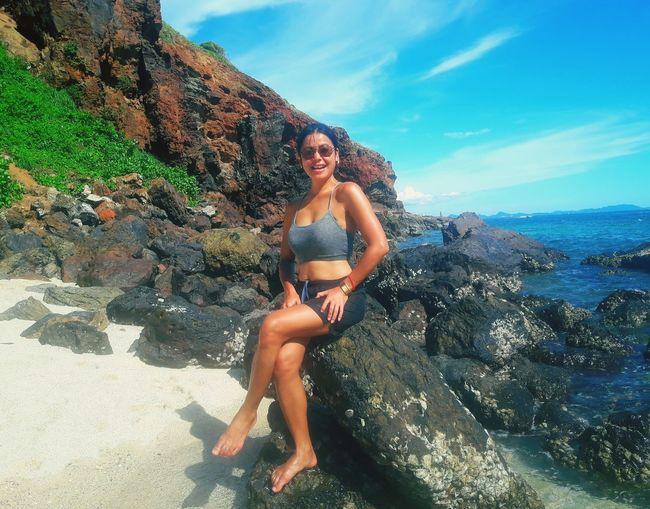 Full length portrait of woman sitting on rock by sea