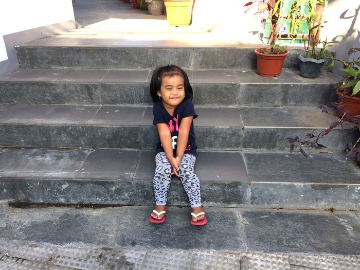 Cute smiling girl sitting on steps