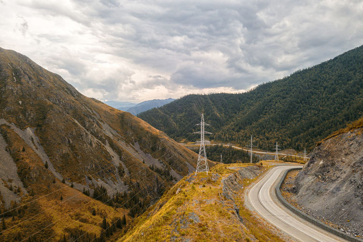 Highway through the mountains, high mountains on each side, power lines and green forest