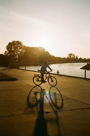Silhouette woman riding bicycle on road by lake against sky