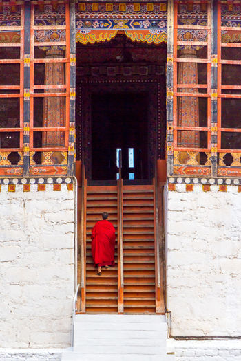 Rear View Of Monk Walking On Monastery Steps