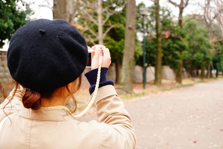 Rear view of woman photographing through camera on road
