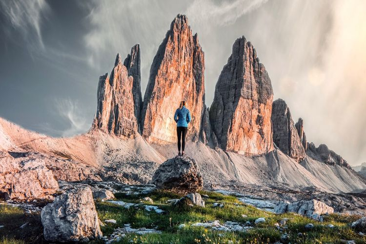 Low angle view of person standing on rock against sky