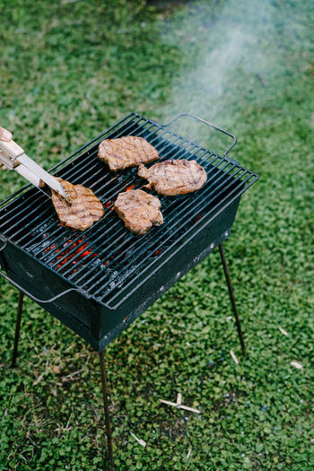 High angle view of meat on barbecue grill in yard