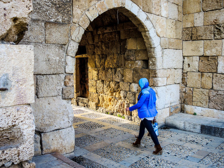 Arch Arched Architecture Building Exterior Built Structure Casual Clothing Day Footpath Full Length History Looking Outdoors Pass Through Person Rear View Side View Stone Wall The Past Walking Wall - Building Feature