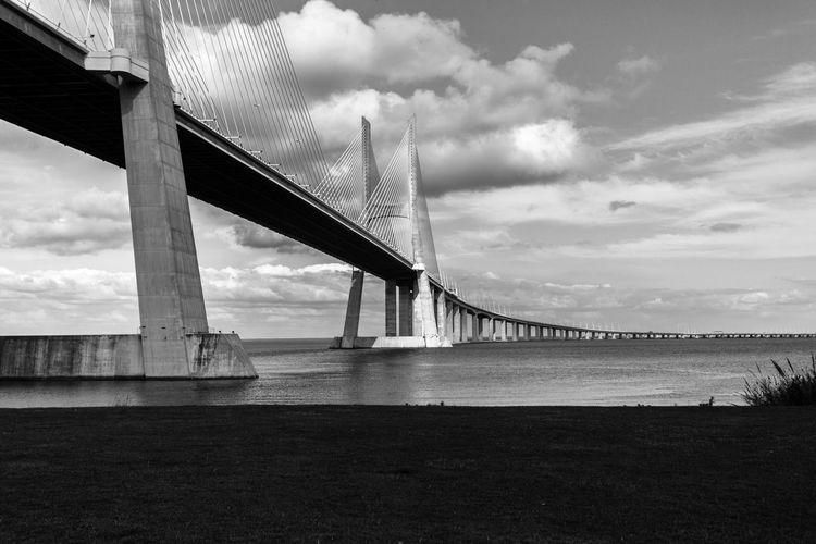 Low Angle View Of Vasco Da Gama Bridge Against Cloudy Sky