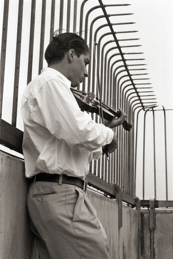 Side view of man playing violin by railing